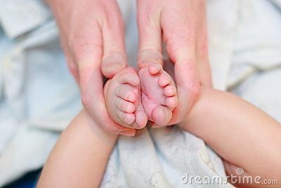 Mother hold baby leg in hand
