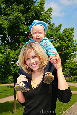 Mother hold child on shoulders outdoor