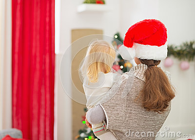 Mother holding baby and looking on Christmas tree