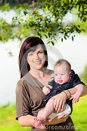 Mother holding baby in park