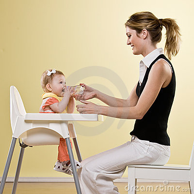 Mother holding bottle for baby in highchair