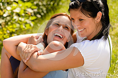 Mother holding daughter in her arms laughing