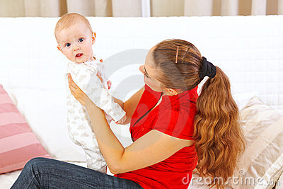 Mother holding intersted baby in hands