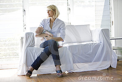 Mother holding sleeping baby on sofa in sunny room