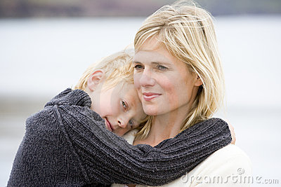 Mother holding son at beach smiling