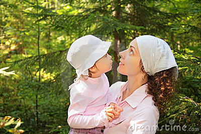 Mother holds daughter on hands in wood