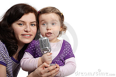 Mother hugs daughter, which sings into microphone Stock Photo