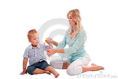 Mother with joyful son playing with soap bubbl