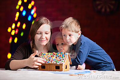 Mother with kids making gingerbread house