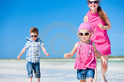 Mother and kids running at beach