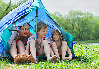 Mother and kids in swimsuit sit in tent