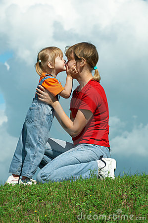 Free Mother Kiss Little Daughter On Green Grass Royalty Free Stock Photos - 5958028