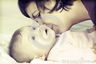 Mother kissing her little baby girl