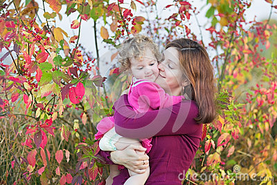 Mother kissing her toddler daughter in garden