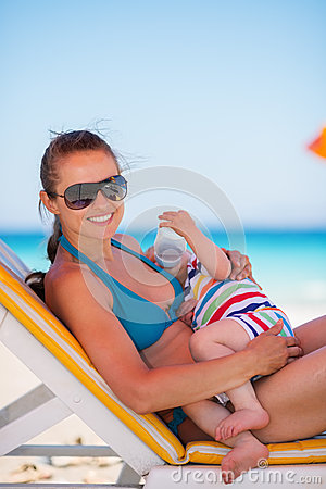 Mother laying on sunbed and holding baby