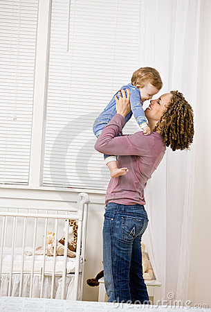 Mother lifting son from crib in bedroom
