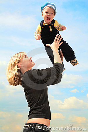 Mother lifts child on hands outdoor