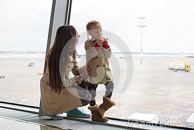 Mother and little daughter looking out the window