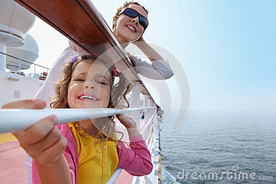 Mother and little daughter stand on board of ship