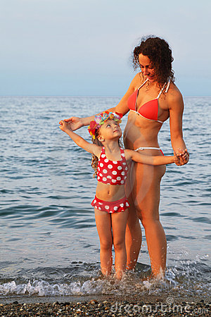 Mother and little daughter standing on beach