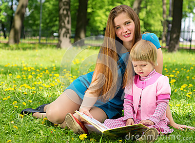 Mother and little girl reading book together