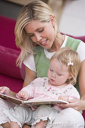 Mother in living room reading book with baby