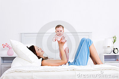 Mother lying  on the bed and playing with baby