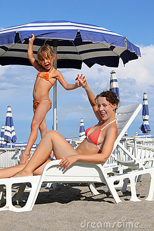 Mother lying on lounger. daughter standing near