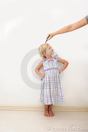 Free Mother Measuring Height Of A Child Stock Images - 15053034
