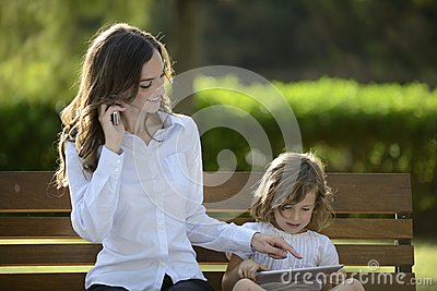 Mother on phone with daughter using digital tablet