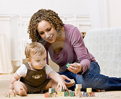 Mother playing with alphabet blocks with her son