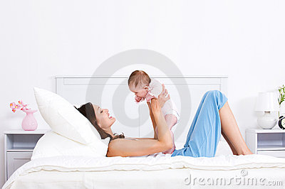 Mother playing with baby on the bed