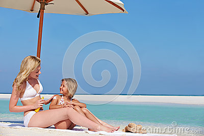 Mother Protecting Daughter With Sun Lotion On Beach Holiday