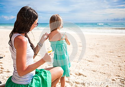 Mother protects her baby from the sun with