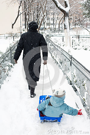 Mother pulling kid on sledge