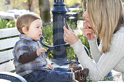 Mother putting on Make Up and Baby Boy on Street