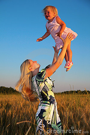 Free Mother Raises Child On Hands In Wheaten Field Stock Images - 6374214