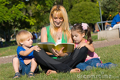Mother reads to children of the book on a glade in
