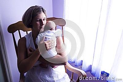 Mother rocking newborn baby