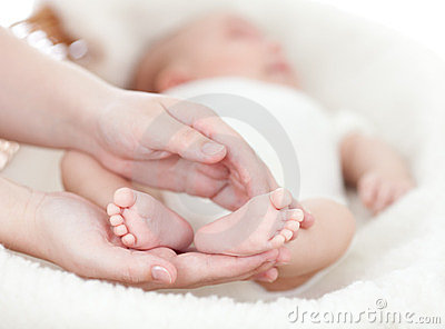 Mother s hands holding small baby s feet