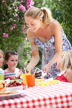 Mother Serving Birthday Cake To Group Of Children