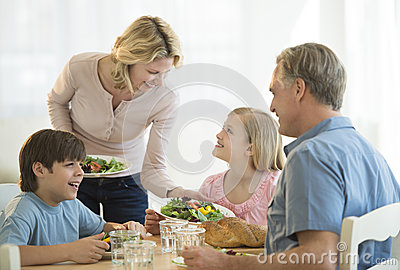 Mother Serving Food To Family At Table