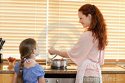 Mother showing her daughter what shes cooking
