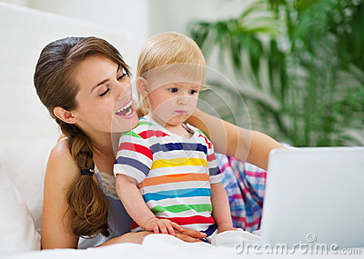 Mother showing something to baby on laptop