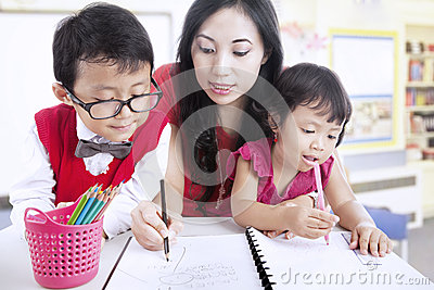 Mother shows children how to write