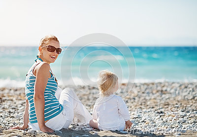 Mother sitting with baby on beach
