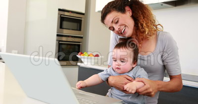 Mother Sitting With Baby Boy On Lap Using Laptop And ...