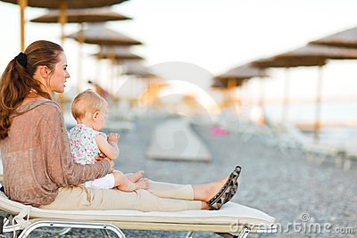 Mother sitting with baby on sunbed on the beach