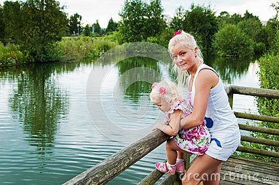 Mother and small daughter by the pond