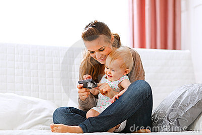 Mother and smiling baby looking photos in camera